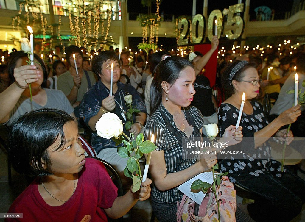 Thai and foreign tourists hold a candlelight vigil during