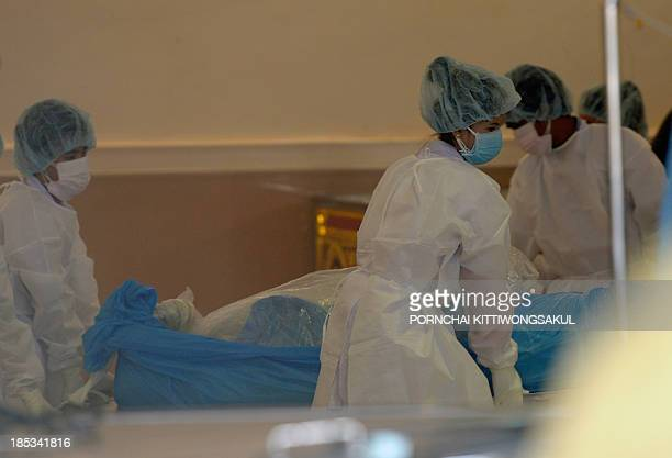 Thai and Lao forensic teams inspect the body of a passenger after it was retrieved from the site of the Lao Airlines turboprop ATR72 plane crash in...