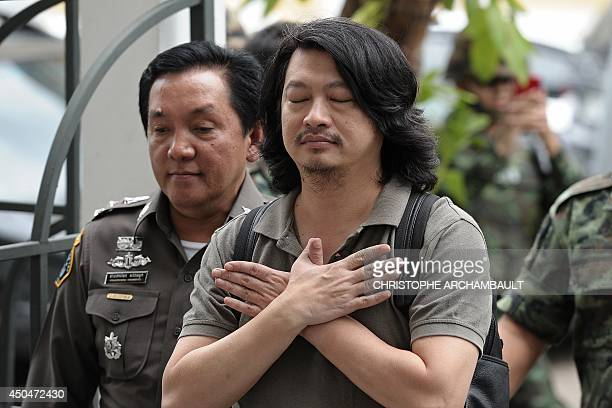 Thai anticoup activist Sombat Boonngamanong gestures as he arrives escorted by police and soldiers at a military court in Bangkok on June 12 2014 The...