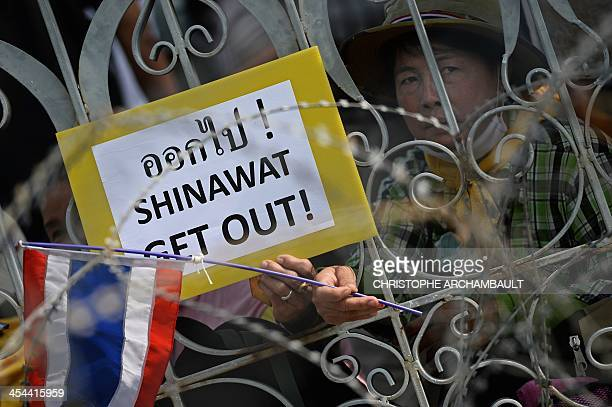 A Thai antigovernment protester holds a sign against prime minister Yingluck Shinawatra and her brother and ex premier Thaksin Shinawatra as they sit...