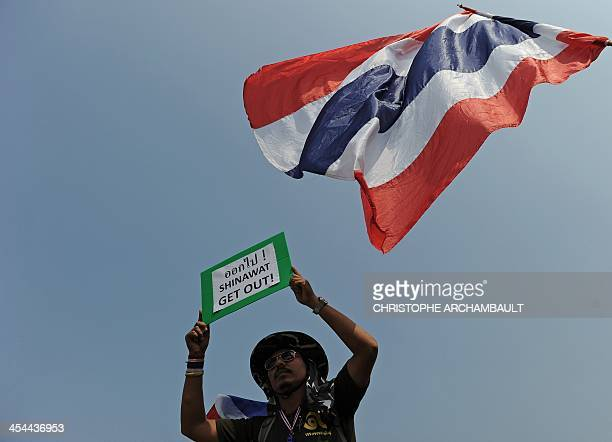 A Thai antigovernment protester holds a sign against Prime Minister Yingluck Shinawatra and her brother and ex premier Thaksin Shinawatra as he...
