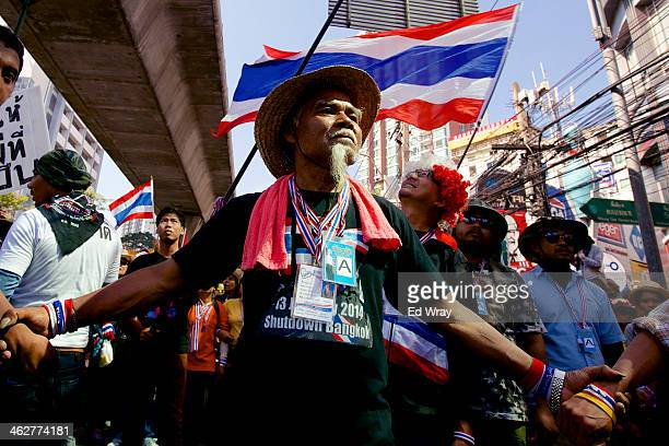 Thai antigovernment protester links arms on a march on January 15 2014 in Bangkok Thailand More violence and instability is feared as the...