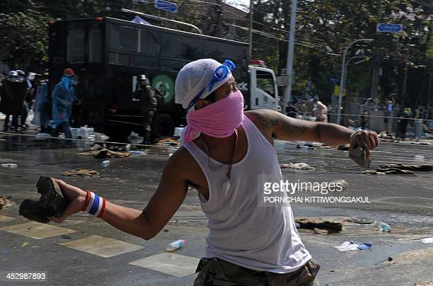 A Thai antigovernment protester throws a brick at riot policemen during a demonstration outside the Government House in Bangkok on December 2 2013...