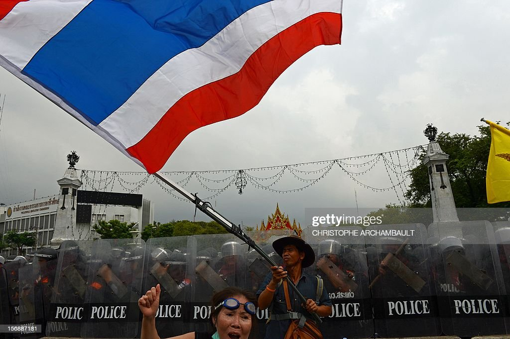 A Thai anti-government protester waves a national flag during a protest in Bangkok on November 24, 2012. Thai police fired tear gas and detained dozens of people as tensions flared at an anti-government protest on November 24 in Bangkok, the scene of several outbreaks of violent unrest in recent years. AFP PHOTO/Christophe ARCHAMBAULT