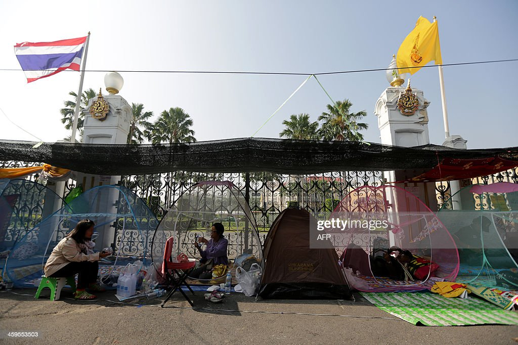 Thai anti-government protesters sit inside mosquito nets outside the Government House in Bangkok on December 28, 2013. A Thai anti-government protester was killed and several others wounded after an unknown gunman opened fire on December 28, at a rally site near the government headquarters in Bangkok, emergency services said.