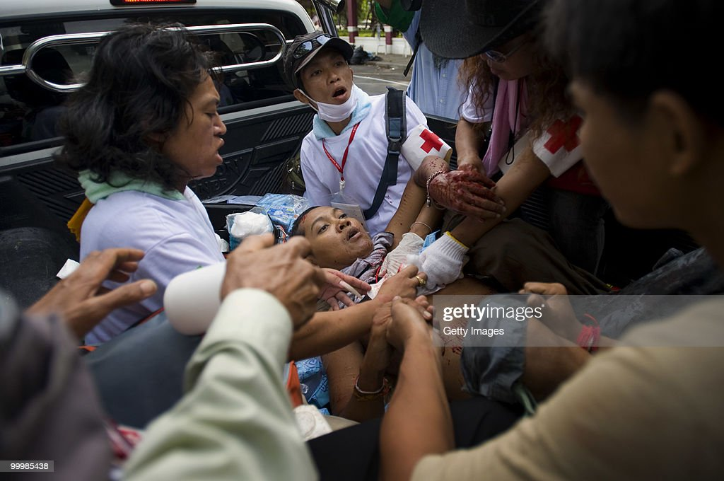 A Thai anti-government red shirt protester is attended to by medics after being shot by the Thai military while aiding a wounded comrade on May 19, 2010 in Bangkok, Thailand. At least 5 people are reported to have died as government forces sought to overrun barricades raised in and around the city centre by anti-government protestors. Red-shirt leaders have now surrendered, ending their blockade in the aftermath of a sixth day of violence, leaving the army in control and a night time curfew to be imposed.