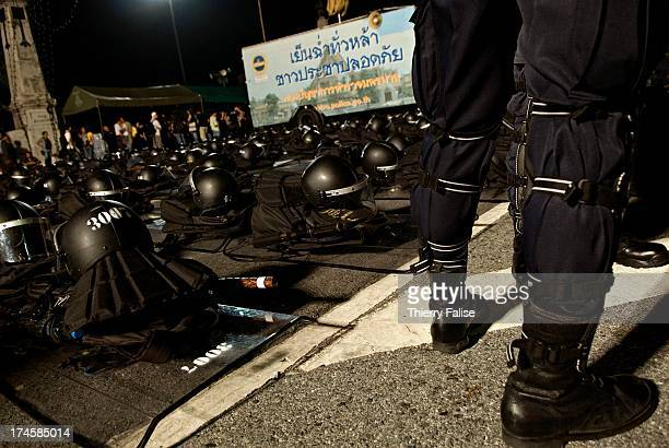 Thai anti-riot policeman stands besides equipment tidied up on the street. Thousands of demonstrators have defyied warnings of a crackdown from the...