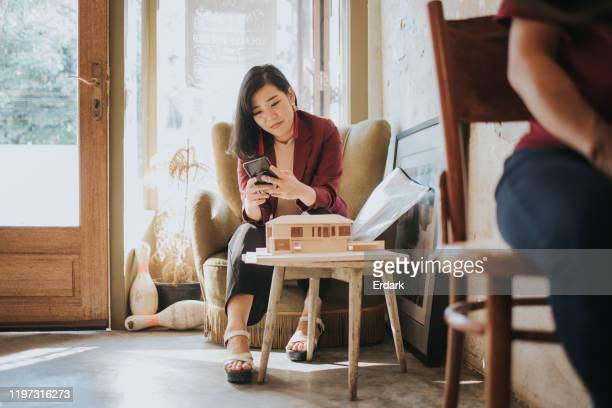 thai architect women chatting to her husband after working while sitting at the cafe - social media marketing stock pictures, royalty-free photos & images