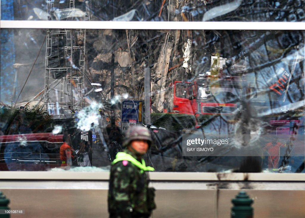 A Thai army soldier walks past a glass window with a reflection of the Central World shopping mall wreckage in downtown Bangkok on May 21, 2010. Thailand picked up the pieces after violence and mayhem triggered by a crackdown on anti-government protests, as the focus swung to recovery and reconciliation in a divided nation. AFP PHOTO / Bay ISMOYO