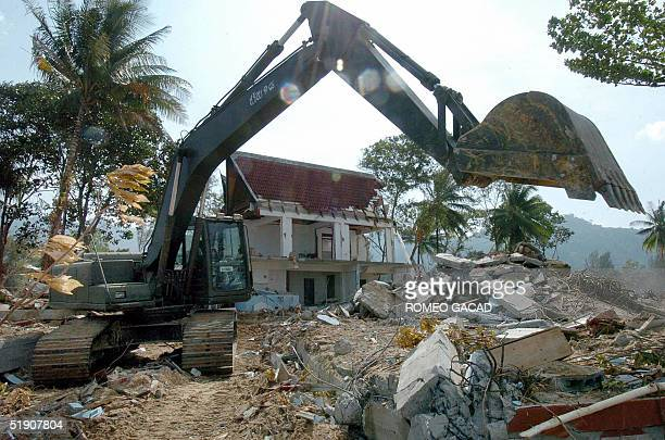 Thai army uses a digger to debris the ruins of hotel buildings in Khao Lak 02 January 2005 in Phang Nga province southern Thailand after massive...