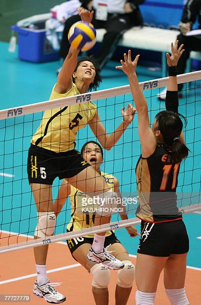 Thai attacker Pleumjit Thinkaow spikes the ball over Japanese blocker Erika Araki during their second round match of the women's World Cup volleyball...