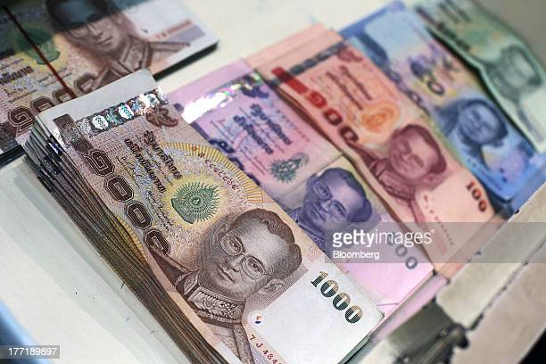 Thai baht banknotes of various denominations sit inside a drawer for an arranged photograph at a Super Rich 1965 Co currency exchange store in...