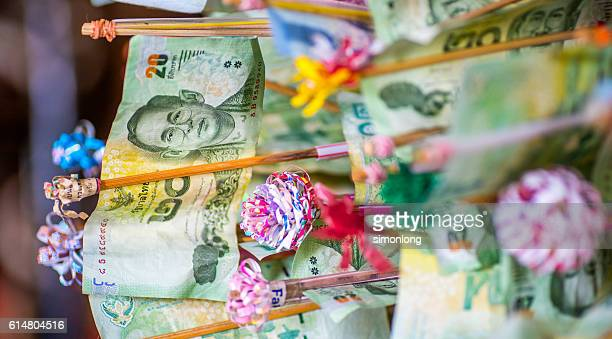 thai bank notes clipped on sticks with handmade paper flowers - king of thailand stock pictures, royalty-free photos & images