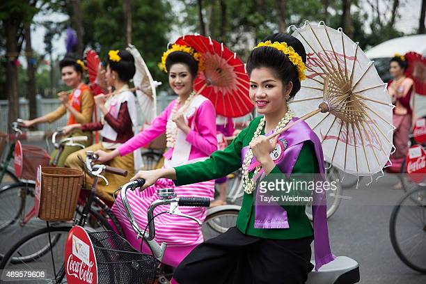 Thai beauty contestants ride bicycles down the street during a Songkran parade on April 13 2015 in Chiang Mai Thailand The Songkran festival marking...