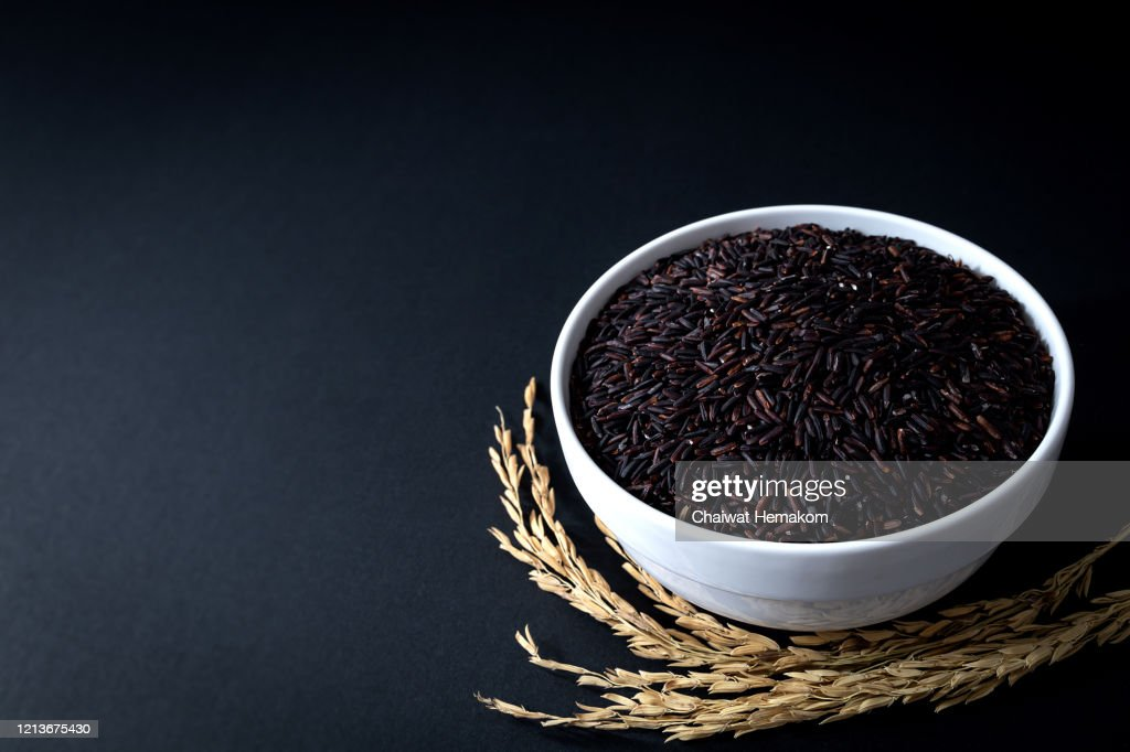 Thai black rice or rice berry in white ceramic bowl on black background. 45 degree angle. close up shot. : Stock Photo