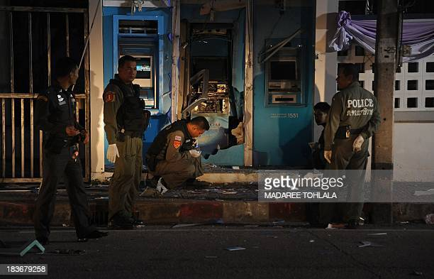 Thai bomb squad members inspect the site of a bomb blast which targeted ATMs in Thailand's restive southern province of Narathiwat on October 9 2013...