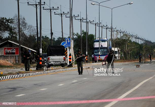 Thai bomb squad members inspect the site of a roadside bomb attack on patrolling soldiers in the Takbai district of Thailand's restive southern...