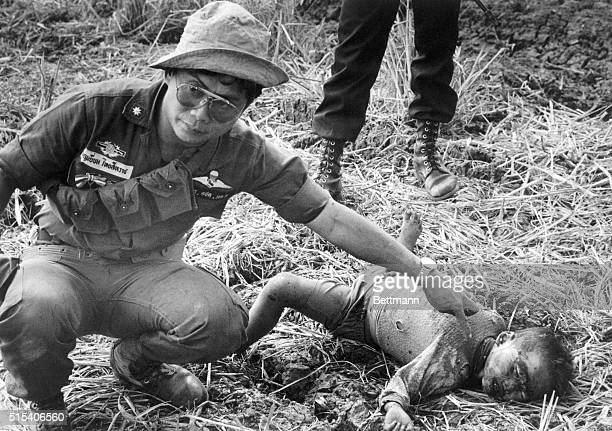Thai border troop officer points to a child whose throat was slashed during a Khmer Rouge raid January 30 to the Thai border villages