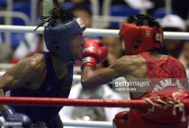 Thai boxer Tusoh Adnan in action with Malaysian boxer Sontaya Wongprates during the quarterfinal of 54 Kilograms category match 12 December at the...