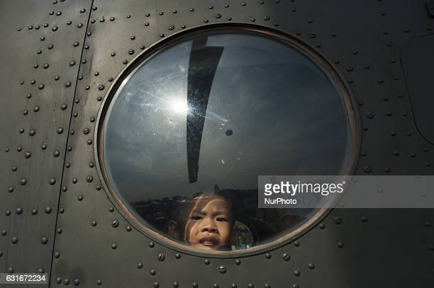A Thai boy looks out from a military helicopter during the National Children's Day event inside a military base in Bangkok Thailand on 14 January 2017