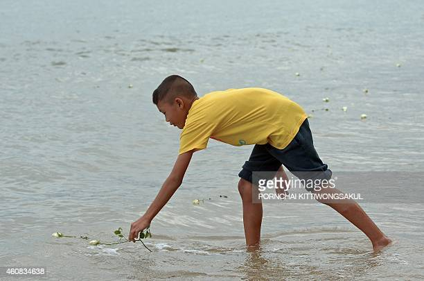 A Thai boy places a rose into the sea near the Ban Nam Khem tsunami memorial park wall as the tenth anniversary of the 2004 tsunami is remembered in...