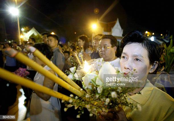 Thai Buddhist devotee holds candles and flowers as she prays during a special worship session to celebrate the Makha Pucha Day Buddhist festival at a...