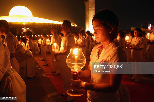 Thai Buddhist devotees carries candles during a religious ceremony to mark Makha Bucha day at Dhammakaya Temple in Pathum Thani province. Makha Bucha...