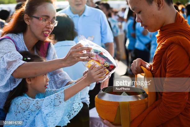 Thai Buddhist devotees give alms to a Buddhist monk as part of celebrate the Queens Sirikit' 86th birthday in Bangkok Thailand 12 August 2018