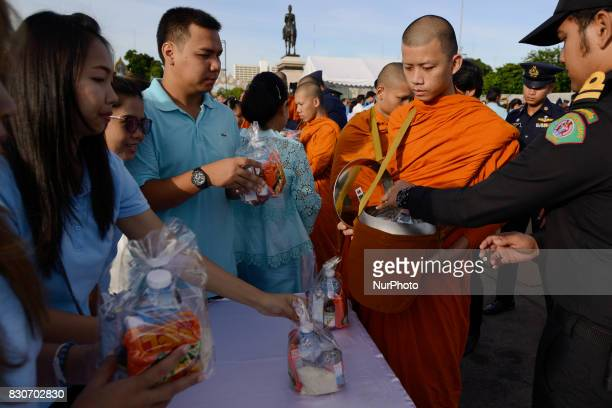 Thai Buddhist devotees give alms to a Buddhist monk as part of celebrate the Queens Sirikit' 85th birthday in Bangkok Thailand 12 August 2017