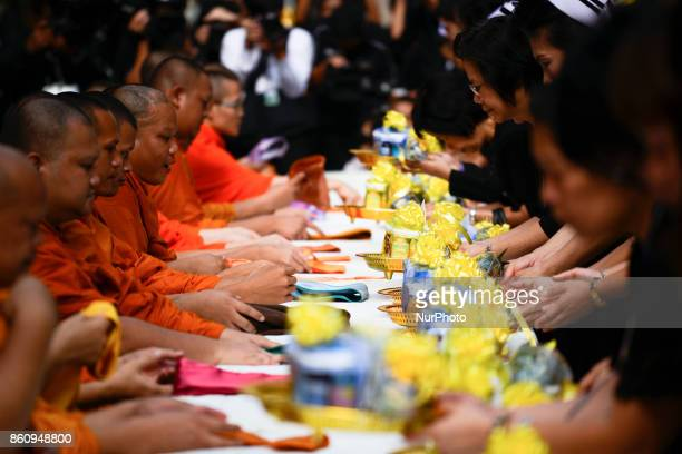 Thai Buddhist devotees give alms to a Buddhist monk at Siriraj Hospital in Bangkok, Thailand, 13 October 2017. King Bhumibol Adulyadej passed away on...