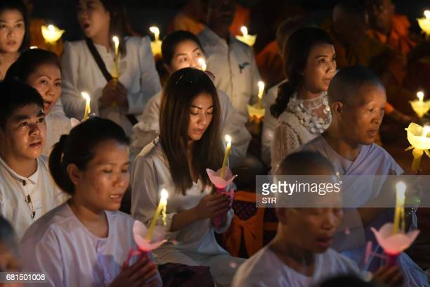 Thai Buddhist devotees hold lighted candles as they offer prayers at The Mahabodi Temple at Bodhgaya on May 10 on the occasion of Buddha Purnima...
