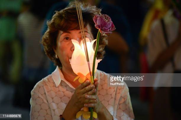 Thai Buddhist lights a candle to celebrate during a ceremony marking Visakha Bucha Day in Bangkok Thailand on 18 May 2019