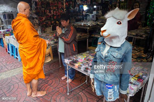A Thai Buddhist monk on alms round in Bangkok's Chinatown
