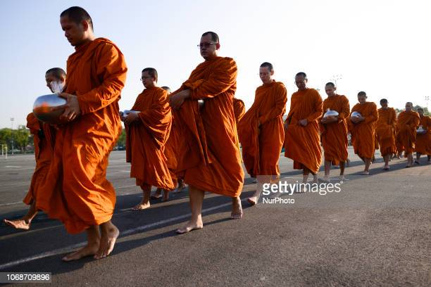 Thai Buddhist monks receive alms as part of in memory of late Thai King Bhumibol Adulyadej on his birthday anniversary at Sanam Luang in Bangkok...