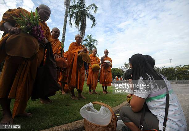 Thai Buddhist monks receive food offerings on the occasion of Asalaha Bucha Day in Thailand's southern province of Narathiwat on July 22 2013 The day...