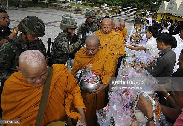 Thai Buddhist monks receive food offerings on the occasion of Visakha Bucha Day in Thailand's southern province of Narathiwat on June 4 2012 Visakha...