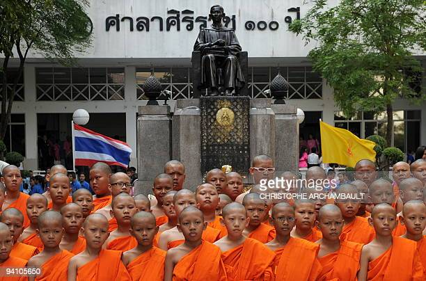 Thai Buddhist novices stand in the courtyard of the Siriraj Hospital where they came to offer prayers for the recovery of Thai King Bhumibol...