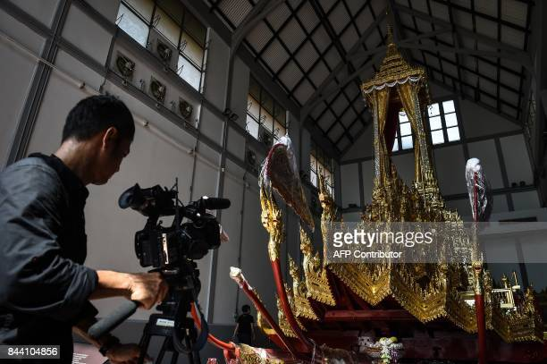 A Thai cameraman films the funeral barge to be used for the cremation of the late Thai king Bhumibol Adulyadej at the National Museum in Bangkok on...