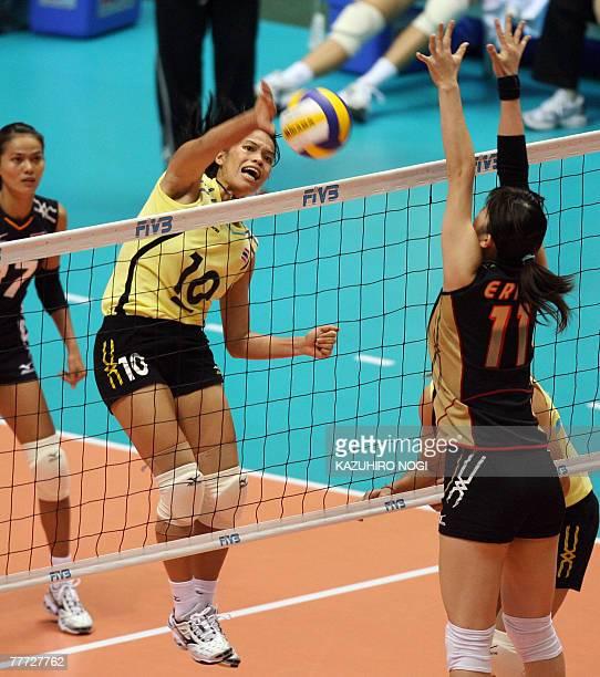 Thai captain Wilavan Apinyapong spikes the ball against Japanese blocker Erika Araki during their second round match of the women's World Cup...
