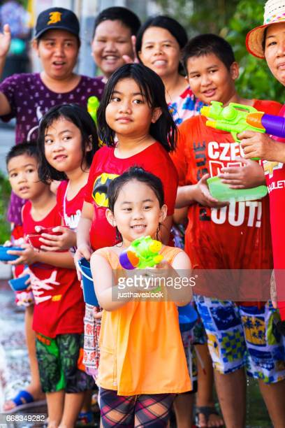 thai children and women at songkran - städtische straße stock pictures, royalty-free photos & images