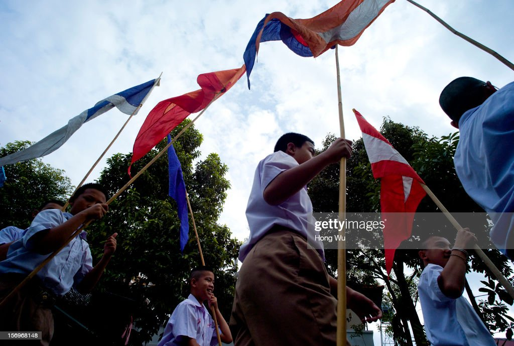 Thai children hold flags for a Buddhist ceremony at Wat Chedi Luang on November 26, 2012 in Chiang Mai, Thailand. Chiang Mai is the largest and most culturally significant city in northern Thailand. It's a former capital of the Kingdom of Lanna (1296-1768) and was the tributary Kingdom of Chiang Mai from 1774 until 1939. In recent years, is has become an increasingly modern city and has been attracting over 5 million visitors each year, of which between 1.4 million and 2 million are foreign tourists.