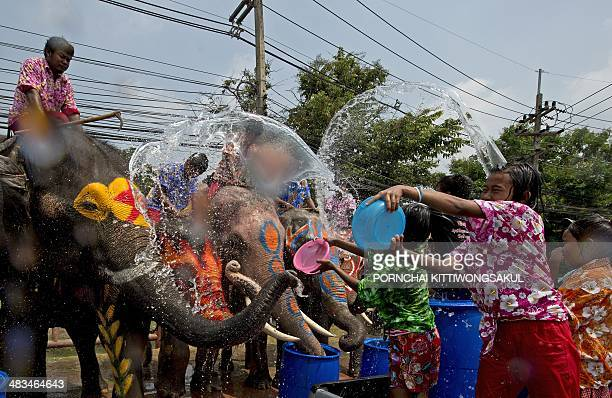 Thai children splash water as they take part in water battles with elephants as people celebrate ahead of the Songkran Festival for the Thai New Year...