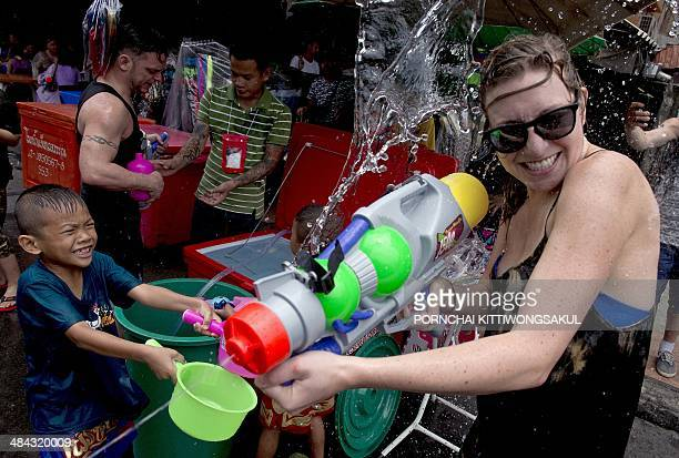 Thai children splash water on a foreign tourist as they take part in water battles to celebrate Songkran Festival for the Thai New Year at Khao San...