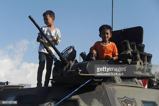 Thai children stand on a military vehicle displayed during celebrations for the National Children's Day at a military base in Narathiwat province on...