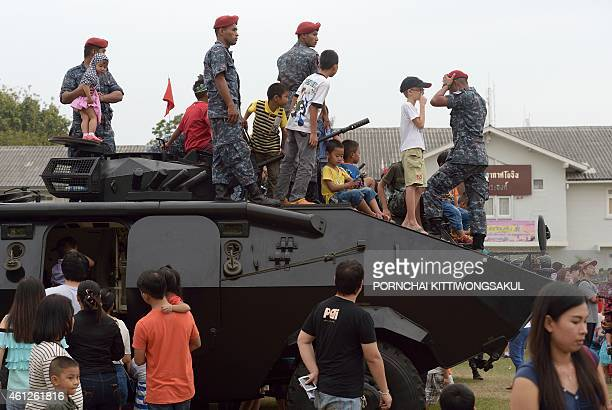 Thai children stand on a military vehicle displayed during National Children's Day at a military base in Bangkok on January 10 2015 Thailand...