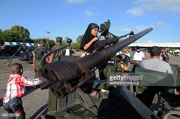 Thai children stand on a military vehicle mounted with a canon displayed during celebrations for the National Children's Day at a military base in...