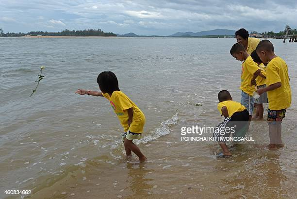 Thai children throw roses into the sea near the Ban Nam Khem tsunami memorial park wall as the tenth anniversary of the 2004 tsunami is remembered in...