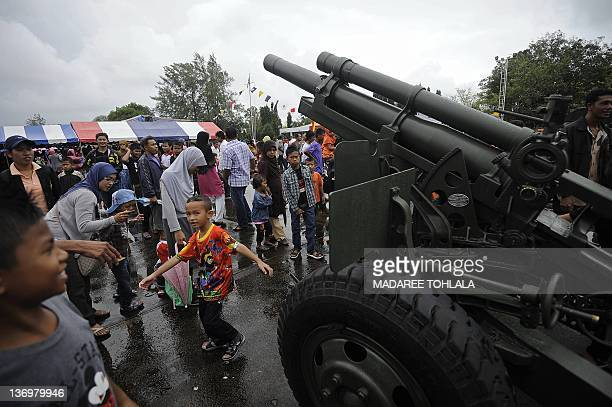Thai children watch a piece of artillery displayed at a Navy camp on the occasion of Children's Day in Thailand's restive southern province of...
