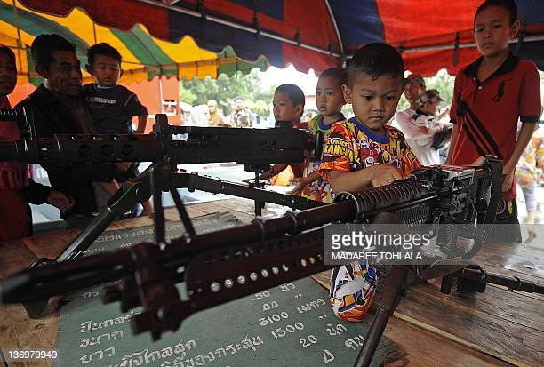 Thai children watch automatic rifles displayed at a Navy camp on the occasion of Children's Day in Thailand's restive southern province of Narathiwat...