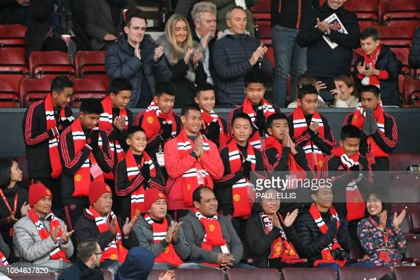 Thai coach Ekkapol Chantawong and members of the Wild Boars football team take their seats in the stand for the English Premier League football match...